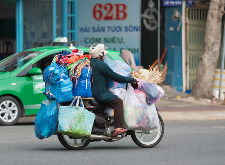 carries: VUNG TAU, VIETNAM - JUNE 10, 2015: An unidentified woman carries lots of bags and sacks by her motorbike. The main means of cargo transportation in Vietnam is motorcycle.