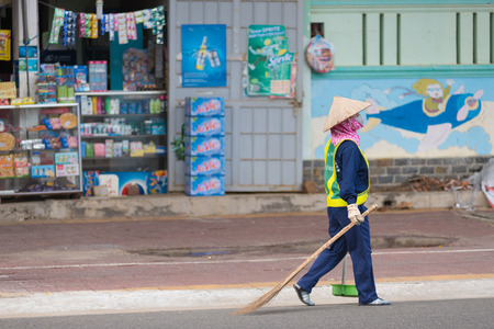 everyday jobs: VUNG TAU, VIETNAM - JUNE 10, 2015: An unidentified dustwoman carries a broom and a dustpan along the road. Due to the climate disposition of garbage is made several times a day.