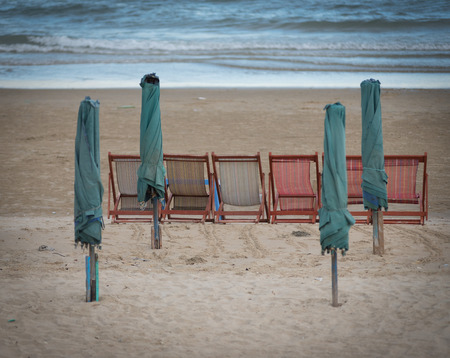 sunshades: folded sunshades and empty lounges at deserted beach, travel industry collapse