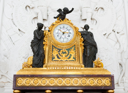 hermitage: ST PETERSBURG - JUNE 30, 2011: A solid golden fireplace clock with black statuettes in one of halls of the Hermitage Museum. Today the collection of the museum contains about 3 million items.