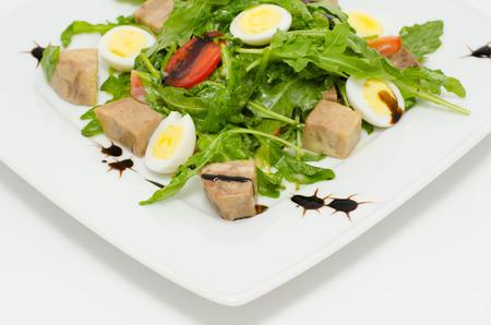 roquette: salad - egg halves, pork cubes, roquette and tomatoes