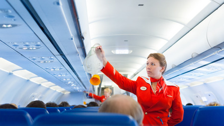 MOSCOW - MAY 28, 2011: Air hostess Yulia of Aeroflot shows how to use an oxygen mask on board. Aeroflot operates the youngest fleet in the world among major airlines, numbering 150 airliners.
