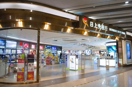 throughput: BEIJING - FEB 16, 2013: Unidentified people walk at a duty free shop at the Beijing Capital International airport. In 2014 it was the busiest airport in the world in terms of passenger throughput. Editorial