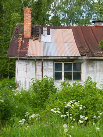 neglected: a neglected country house in an overgrown yard Stock Photo