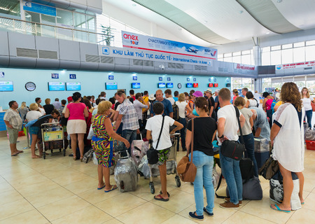 to queue: CAM RANH, VIETNAM - OCTOBER 8, 2015: Unidentified Russian tourists check in at the Pegas Fly air company. Pegas Touristik is a Russian tour operator possessing 50 offices in Russia.