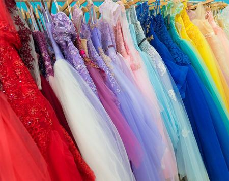 anochecer: damas de noche y de boda de los vestidos en perchas, en alquiler