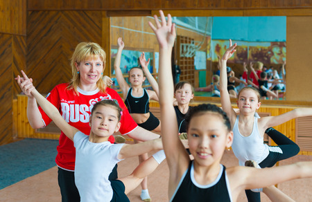 barre: ULAN-UDE, RUSSIA - APRIL 28, 2011: Trainer Svetlana Bogatykh coaches girls in Gratsia rhythmic gymnastics studio, City Palace of Childrens Arts, the biggest centre offering childrens hobby circles. Editorial