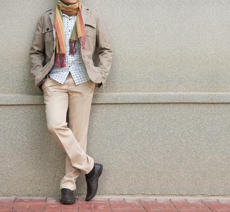 moda: Homem elegante em calças bege e jaqueta contra a parede de pedra