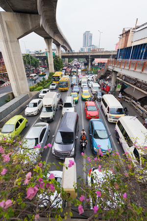 thailander: BANGKOK - DECEMBER 15, 2015: Many vehicles move near the Victory Moment. Transport in Thailand is varied and chaotic, with no one dominant means of transport.
