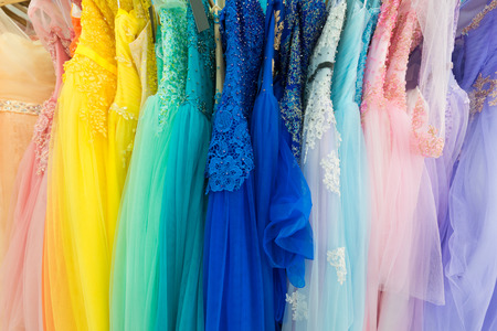 draped: ladies evening and wedding dresses on hangers, for rent