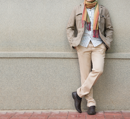 checkered scarf: fashionable man in beige trousers and jacket against stone wall Stock Photo