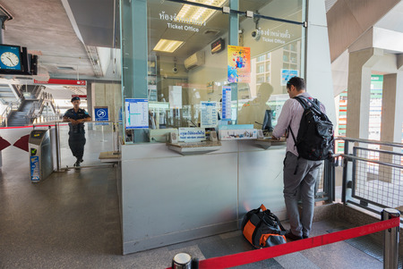 thailander: BANGKOK - DEC 17, 2015: An unidentified tourist buys a ticket to the Suvarnabhumi airport at the Phaya Thai station. It is a rapid transit station of Airport Rail Link BTS Sukhumvit Line. Editorial