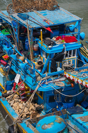fishery: blue fishers boat stuffed with odds and ends