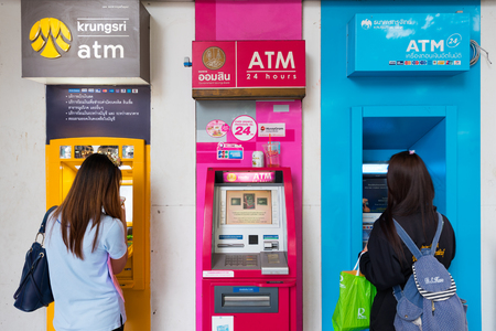 cash back: BANGKOK - DECEMBER 15, 2015:  Two unidentified young women withdraw cash at ATMs at the Victoria Monument bus stop. Editorial