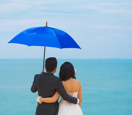 luna de miel: novia y el novio vistazo a mar azul coloca bajo el paraguas Foto de archivo