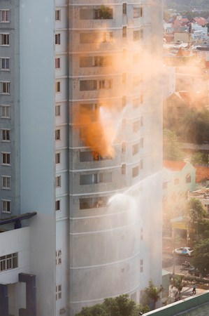 rise: firemen fight the fire in high rise, victims signal with orange smoke and white cloths in windows Stock Photo
