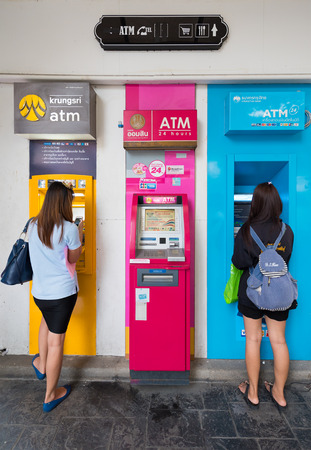 withdraw: BANGKOK - DECEMBER 15, 2015:  Two unidentified young women withdraw cash at ATMs at the Victoria Monument bus stop. Editorial