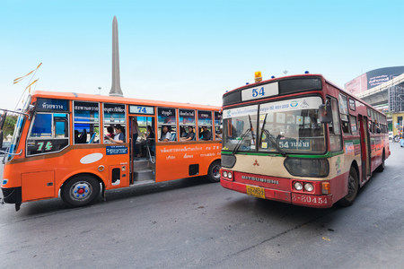 BANGKOK - DECEMBER 15, 2015: Public buses move by the Victory Monument bus stop. Transport in Thailand is varied and chaotic, with no one dominant means of transport. Zdjęcie Seryjne - 54683907