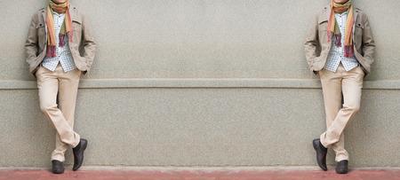 Hombres de moda en pantalones beige y chaquetas contra la pared de piedra