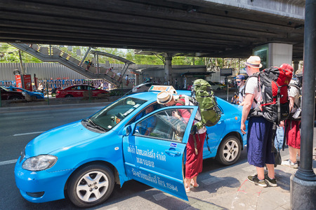 thailander: BANGKOK - MARCH 16, 2016: Unidentified tourists with backpacks get a taxi by the Phaya Thai station in the center. MasterCard ranked Bangkok as the global top destination city.