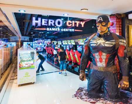 entertaining area: BANGKOK - MARCH 16, 2016: Children and adults play on game machines at the Hero city at the MBK Center, a large shopping mall. Bangkok is one of the worlds top tourist destination cities.