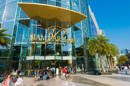 centres: BANGKOK - MARCH 17, 2016 : People walk in and out of the Siam Paragon Shopping mall. It is one of the biggest shopping centres in Asia.
