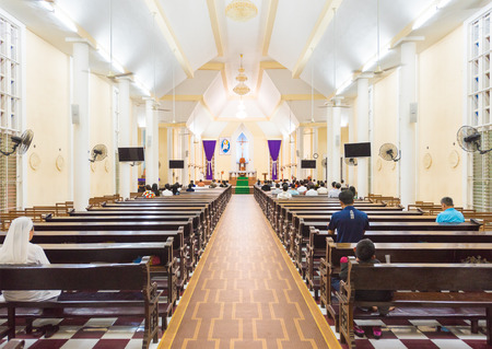 church people: VUNG TAU, VIETNAM - MARCH 24, 2016: Unidentified people sit at public worship in the Nha tho Vung Tau Catholic church. Vietnam has the fifth largest Catholic population in Asia.