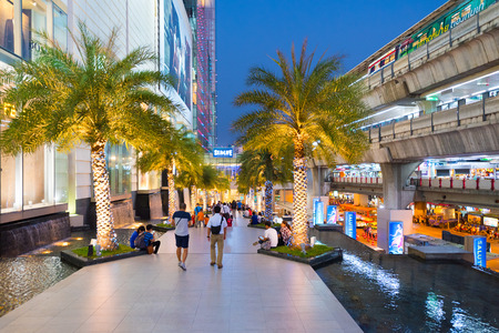 paragon: BANGKOK - MARCH 17, 2016 : People walk along an alley between the Siam Paragon Shopping mall and the Siam sky train station. It is one of the biggest shopping centers in Asia.