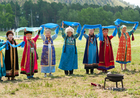 naadan: ULAN-UDE, RUSSIA - JULY 17, 2010: Senior delegates of the 4th General Session of World Mongolians Convention perform a national Buryat round dance - yookhor. It is performed according to solar motion.