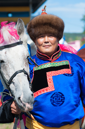 naadan: ULAN-UDE, RUSSIA - JULY 17, 2010: A Buryat man stands by his horse at the 4th General Session of the World Mongolians Convention, an international organization founded in 2006 in Ulaan-Baatar.