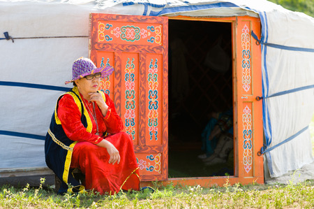 naadan: ULAN-UDE, RUSSIA - JULY 17, 2010: A Buryat woman sits by a yurt during the 4th General Session of the World Mongolians Convention. People from Russia,  Mongolia and China attended the meeting.