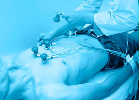 attaches: doctor attaches sensors on patient for taking his electrocardiogram Stock Photo