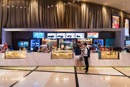 paragon: BANGKOK - MARCH 17, 2016 : Unidentified people buy food at a snack bar of Paragon Cineplex in the Siam Paragon shopping mall. With 16 screens and 5,000 seats, it is Thailands largest movie theater. Editorial