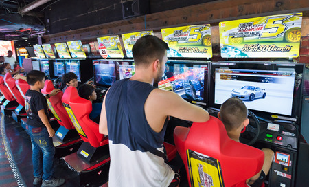machines: BANGKOK - MARCH 16, 2016: Unidentified young men and teenagers play on game machines at the Hero city at the MBK Center, a shopping mall. Bangkok is one of the worlds top tourist destination cities. Editorial