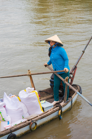 can tho: CAN THO, VIETNAM - MAY 17, 2016: An unidentified woman sells various kinds of rice from her motor boat. Can Tho is the fourth largest city in Vietnam, and the largest city in the Mekong Delta.