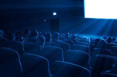 viewers watch a 3D motion picture in special glasses, blue toning