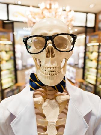 smock: human skeleton in black glasses, bow tie and doctors smock Stock Photo
