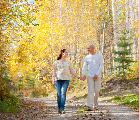 walk in: happy married couple - husband and his pregnant wife walk in autumn forest Stock Photo