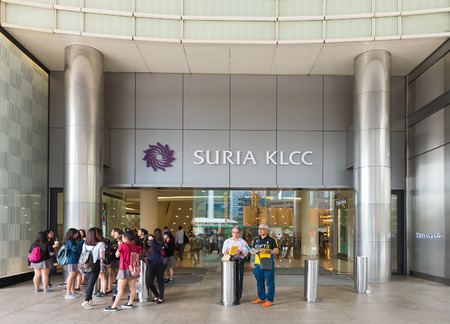 metropolis: KUALA LUMPUR - JUNE 15, 2016: Unidentified people stand by a lateral portal of the Suria KLCC. The shopping mall is located in the Kuala Lumpur City Centre district near the famous Petronas Towers.