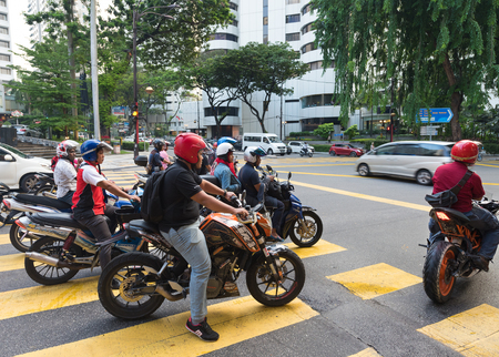 KUALA LUMPUR - JUNE 15, 2016: Unidentified motorcyclists and vehicles stand at a traffic light in the city center. As in other Asian countries motorcycle is the most popular and available transport vehicle.