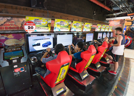 entertaining area: BANGKOK - MARCH 16, 2016: Unidentified young men and teenagers play on game machines at the Hero city at the MBK Center, a shopping mall. Bangkok is one of the worlds top tourist destination cities. Editorial