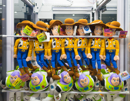 toy story: BANGKOK - MARCH 16, 2016: Buzz Lightyear and Woody toys, Toy Story characters, are in a claw crane at MBK mall. Toy Story is an American animated film produced by Pixar and released by Walt Disney. Editorial