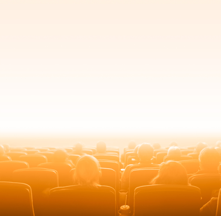 motion picture: viewers watch motion picture at movie theatre, orange toning, copy space Stock Photo