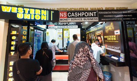 currencies: KUALA LUMPUR - JUNE 15, 2016: People send and exchange money in the Suria KLCC shopping mall. The mall is located in the Kuala Lumpur City Centre district near the famous Petronas Towers.