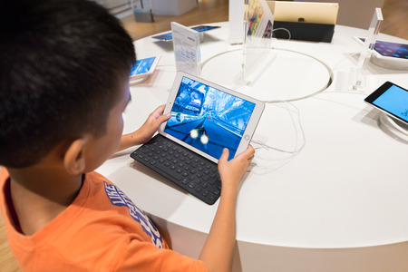 marketed: KUALA LUMPUR - JUNE 15, 2016: A boy plays a computer race on an iPad with a keyboard in Suria KLCC mall. iPad is an iOS based line of tablet computers designed and marketed by Apple Inc.