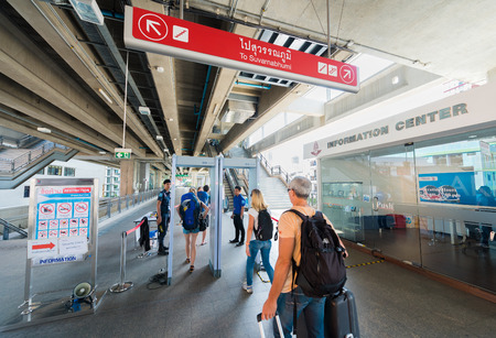 BANGKOK - DEC 17, 2015: Two Thai policemen examine tourists at a security check of Phaya Thai station. It is a rapid transit station of Airport Rail Link BTS Sukhumvit Line.