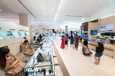 centres: BANGKOK - MARCH 17, 2016: People walk around jewelry and watches shops in the Siam Paragon mall. It is one of the biggest shopping centres in Asia.