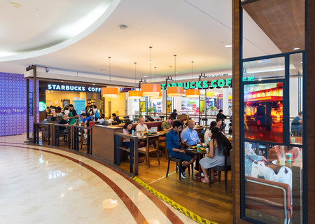 general store: KUALA LUMPUR - JUNE 15, 2016: People sit at the Starbucks coffee in Suria KLCC mall. Starbucks is the largest coffeehouse company in the world with 23,305 stores in 65 countries.