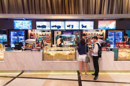 paragon: BANGKOK - MARCH 17, 2016: Unidentified people buy food at a snack bar of Paragon Cineplex in the Siam Paragon shopping mall. With 16 screens and 5,000 seats, it is Thailands largest movie theater.