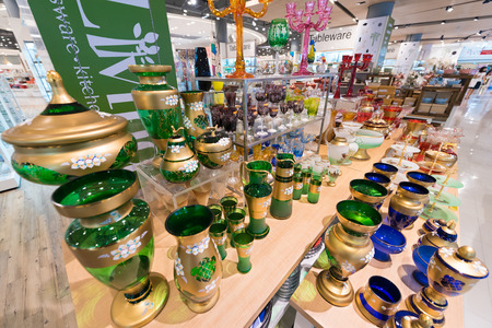 housewares: BANGKOK - MARCH 17, 2016: Various green and colorful glass utensils in the Living store in Siam Paragon mall, one of the biggest shopping centers in Asia. Editorial